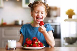 cosa-mangiare-quando-fa-caldo-bambina-che-ride-mentre-mangia-fragole-rosse-in-cucina