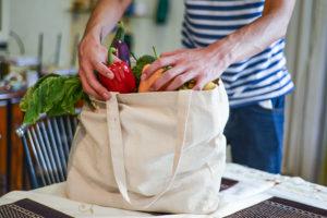 Come-essere-più-sostenibili-borsa-tela-ragazzo-maglia-a-righe-blu-e-bianche-in-cucina-valleitalia
