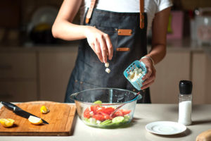 Abbinamenti-particolari-in-cucina-feta-insalata-anguria-e-cetrioli-ragazza-in-cucina-con-grembiule-tagliere-di-legno-e-ciotola